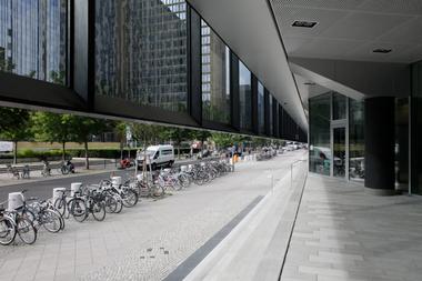 Die bedruckte Glashaut hängt über dem Sockel in der Luft; darunterhergetaucht gelangt man ins Gebäude (hier der Haupteingang)