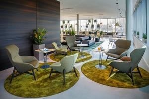 Im Bistro sorgen A-Bench, A-Chair und A-Table sowie der fina club-Hochtisch in Kombination mit fina wood-Barhockern für eine bequeme Essenspause. Die Loungebereiche laden zum Entspannen zwischendurch ein. Sie sind mit ray lounge in der niedrigen sowie in der Hochlehner-Variante und plot ausgestattet. Ergänzt werden sie durch plot- und höhenverstellbare lift-Beistelltische. Der begrünte Raumteiler PARA VERT ergänzt diese Zone