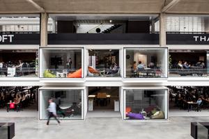 Aus den Mezzaninen treten verglaste Boxen, die als Besprechungsräume dienen, hervor