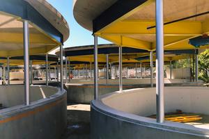Die Garten-Studios bestehen aus gut tischhohen Betonringen, in welche die Stahlstützen eingegossen sind, die mit der verschweißten Stahlträgerkonstruktion die einfache Dachplatte halten. Verbunden werden Betonring und Dach abschließend durch gekrümmte Acrylscheiben, deren Einzelelemente mittels Silikon verklebt sind. Gehalten werden die Scheiben über Stahlwinkel, die sichbar in den Beton und das Holz verschraubt sind