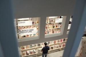 Die Ausstellung von oben. Besucher verweilen gerne bei den Heften und blättern darin