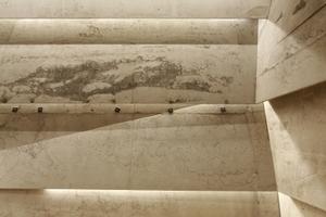 """Die Saalwand hinter dem Musikern. Der Beton lebt von den Schalungs""""fehlern"""", die auch aus Gründen der Akustik nicht ausgebessert wurden"""