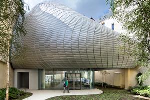Das Tragwerk des amorphen Daches ist in drei Schichten aufgebaut: gebogene BSH-Träger,<br />gekrümmte Isolierverglasung und Aluminiumlamellen als Sonnenschutz