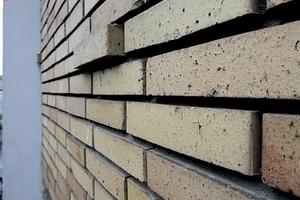 Über den Versatz einzelner Klinkersteine aus der Verbundebene heraus gewinnt die flächige Fassade die nötige Lebendigkeit