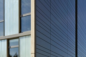 """Die Seitenwände wurden mit vorgehängten Metallkassetten verkleidet. Gut zu sehen ist hier auch der geschossumschließende, graue Metallrahmen auf der """"Barcode""""-Fassade"""
