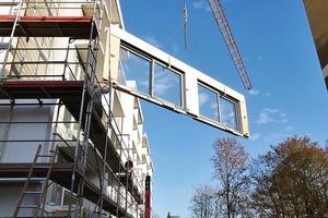 """<div class=""""13.6 Bildunterschrift"""">Die fertigen Fassadenelemente werden mit dem Kran in Position gehoben</div>"""