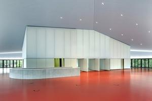 Der Boden aus rotem Kautschuk setzt einen starken Farbakzent gegen Textilwand- und Brüstungsflächen<br />