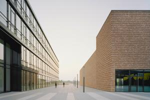 Der Blick Richtung Westen: Das Bürogebäude mit voll verglasten Geschossen, gegenüber das Besucher- und Kundenzentrum