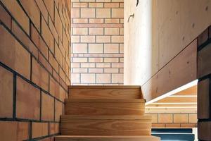 Links im Bild die bis unter das Dach aufsteigende tragende Ziegelwand, an der die Holztreppe in die oberen Geschosse führt