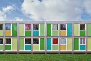 Mit Farben inszenieren die Architekten die Holzmodule: Grüntöne sind dort zu sehen, wo sich die Unterkunft der Natur zuwendet