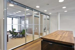 """<div class=""""4.1 Bildunterschrift"""">Im Innenausbau kamen die Structural-Glazing-Systemtrennwände und Türelemente Fecostruct von feco<sup>®</sup> zum Einsatz. Die transparenten Elemente bieten neben flächenbündiger Optik auch Schalldämmwerte Rw,p von bis zu 47dB und die Möglichkeit Jalousien als Sicht-<br />schutz in die Elemente zu integrieren</div>"""