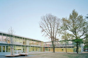 Links Schule, rechts eingegrabene Sporthalle mit Spieldeck oben drauf
