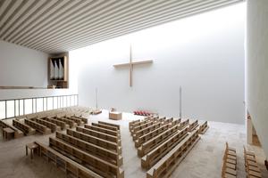 Kircheninnenraum: Blick auf Altarraum und Orgel auf der Empore. Das große Kreuz an der nördlich liegenden Altarwand stammt wie Ambo und Tabernakel vom Künstler Jorge Pardo