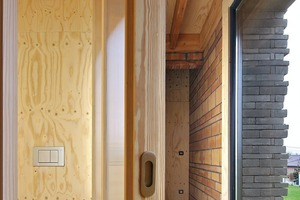 Im Zentrum des ersten Obergeschosses und über der Küche liegen das Badezimmer, das separate WC und ein zusätzlicher, kleiner Abstellraum. Die Wände dieser kompakten Box, um die ein Gang verläuft, sind Holzständerwände