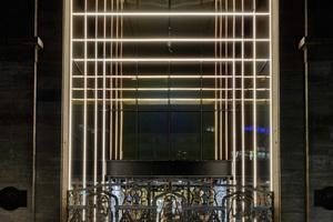 Der 8 m hohe Eingangsbereich empfängt den Besucher mit einer tiefenwirksamen Gestaltung. Zwischen die eingefärbten Spiegelgläser wurden schmale Lichtlinien eingesetzt