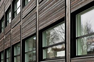 Die neue Holz-Alu-Fassade bekam eine Verschalung aus heimischem Fichtenholz, das im Shou-Sugi-Ban Verfahren wetter-fest gemacht worden war. Das Fassadenkonzept wurde mit als Passivhaus-Fassade umgesetzt