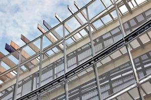 Die sich über die gesamte Gebäudelänge erstreckende Gewebefassade<br />aus Edelstahl besteht optisch aus drei horizontal verlaufenden Gewebebändern. Die transparente Fassadenverkleidung ermöglicht die unverstellte Sicht aus den Klassenräumen nach außen