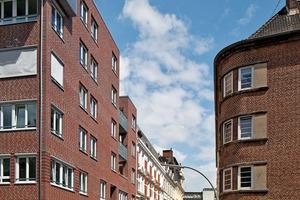 rechts:Da Maisonettewohnungen für den Bauherrn einen teuren Wohntypus darstellen, mussten die Architekten Möglichkeiten finden, um die höheren Kosten auszugleichen. Dies gelang, indem die im Baustufenplan vorgeschriebene maximale Gebäudehöhe um zwei weitere Geschosse überschritten wurde und dadurch weitere Wohnungen realisiert werden konnten