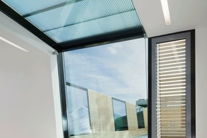 Außenbündig und Über-kopf folgen die Fenster den Dachneigungen. Ein lichtlenkendes Isolierglas mit Sonnenschutzbeschichtung Arcon Sunbelt Silber 39/25 und Zwischenraumfolie erreichen einen U-Wert von 6,0 W/m²K. Bei direktem Sonneneinfall bekommt die Überkopfverglasung elegante Markisen, die geräuschlos unten und oben zugefahren werden können<br />
