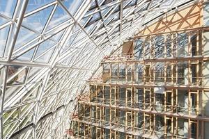 links: Das gekrümmte Glasdach bildet den wesentlichen Teil der klimatischen Hülle der Atrien und wurde als wärmegedämmte Aluminiumkonstruktion mit Zwei-Scheiben-Isolierverglasung ausgeführt <br /><br />
