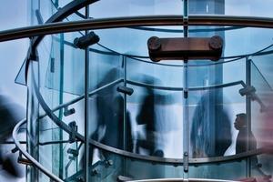 An den Außenseiten sind die Stufen über zwei Anker am Ganzglasgeländer befestigt, das aus gebogenen Parallelogrammen gefügt wird