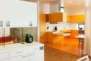 Herdplatte und Spüle sind rollstuhlgerecht, alle Möbel orange. Man kocht und isst gern gemeinsam<br />