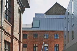 Die minimalistisch-kühle und dennoch haptisch und visuell attraktive Außenhaut der Neubauten erzeugt einen reizvollen Kontrast zur warmen Ausstrahlung der Backstein- und Putzfassaden mit ihren historischen Holzfenstern