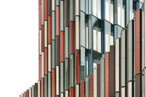 Die Farben der Fassade orientieren sich an der Umgebung. Die Grüntöne weisen in Richtung Palmengarten, die roten Flächen orientieren sich zur Zeppelinallee und beziehen sich auf den ortstypischen Mainsand und die graublauen Elemente nehmen die Farben der KFW-Bank auf<br />