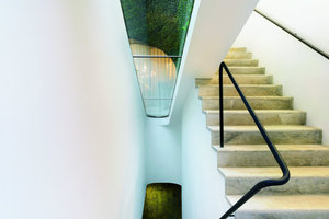 Nach unten verändert sich der weiße Treppenraum zu einer organischen Form, deren grüne Wände den Innenraum wie eine moosbewachsene Höhle erscheinen lassen. Hier wird deutlich, dass das Gebäude eine Verschmelzung von innen-außen und natürlich-<br />künstlich erreichen will
