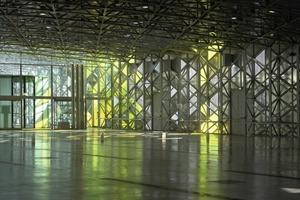"""<div class=""""13.6 Bildunterschrift"""">Dreiecke mit farbigen Sonnenschutzgläsern in gelb oder grün sorgen im Innenraum – wie hier im Eingangsbereich – für Lichteffekte</div>"""
