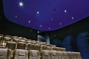 Nahe dem Eingangsbereich befindet sich der kleine Kinosaal als freistehende Rundform unter dem Konferenzraum. Die Aluminiumlamellen außen erinnern an einen Flugzeugrumpf