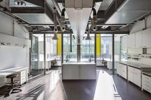 Die Labore basieren auf einem 1,15m-Achsmaß. Die Raumbreite von 3 x 1,15m = 3,45m erlaubt das Aufstellen zweier 90cm-tiefer Tische mit einem gesetzlichen Mindestabstand von 1,45m, (inklusive 15cm Innenwandstärke und 5cm Toleranz)
