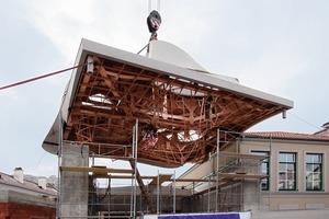 Mit einem 100 t-Kran wird das komplette Dach auf das Gebäude aufdockt<br />
