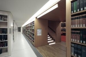 Rechts blickt man in den Lesesaal, der von Regalwänden eingefasst ist. Die Treppenstufen hinauf sind beleuchtet.