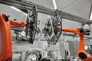 Bei dem kernlosen robotischen Wickelprozess werden in Harz getränkte Glas- und Carbonfasern auf von zwei kooperierenden 6-Achs-Industrieroboter geführten Rahmen (Effektoren) gewickelt