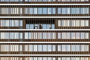 Vom ersten bis zum siebten Obergeschoss der Bürogebäude dienen die Glaslamellen als Sonnenschutz. Auch an die elektronische Steuerung des Lamellensystems war u. a. die Anforderung gestellt, dass sie einen optimalen Schutz vor der Sonne bieten soll. Das System arbeitet mit einer komplett verdeckten Mechanik, die unsichtbar in den Tragprofilen aus Aluminium integriert sind<br />