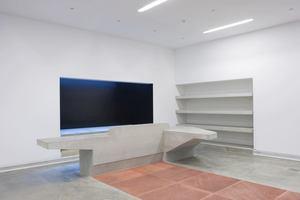 Empfang mit Betonmöbel hinter Kupferteppich. Dahinter: Licht von oben in Wandschacht