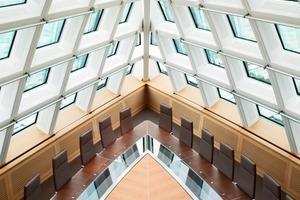 Unter der Gebäudespitze steht ein dreiecksförmiger Konferenztisch vor einem riesigen Flachbildschirm<br />