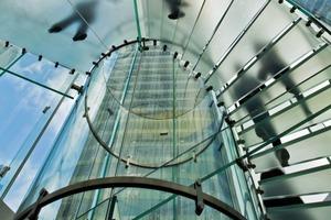 Die gläserne 1,70m breite Treppenanlage, ist erst beim Betreten des Stores voll erlebbar. Sie wendelt sich mit einem Durchmesser von 6,25m um 4,90m in die Tiefe. Die 32 Stufen und das Zwischenpodest bestehen aus 4-lagigem VSG
