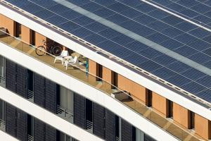 Auf der Straßenseite wurde die leicht gefaltete Fassade mit 348 PV-Modulen bestückt, die zusammen mit weiteren 750 Modulen auf dem Pultdach einen jährlichen Stromertrag von 300000 kWh erzeugen