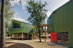 Drei Baumhäuser, die durch überdachte Stege miteinander verbunden sind, fügen sich geschickt in ein Wäldchen ein und gruppieren sich um einen Spielhof