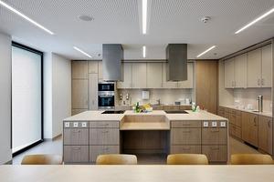 """<div class=""""13.6 Bildunterschrift"""">Küche- und Medikamentenausgabe. Das Mobiliar wurde gemeinsam im Team: Architekt, Bauherr und Belegschaft entwickelt</div>"""