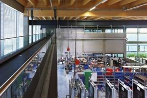 Das Dachtragwerk der mittig angeordneten Montagehalle mit integriertem Lager ist eine reine Holzkonstruktion, die die große Dimension mit möglichst wenigen Stützen überspannt und zudem für ein angenehmes Raumklima und Belichtung sorgt