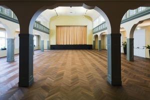 Im Veranstaltungssaal wird das Bodenniveau um 15cm angehoben, die Galeriebrüstungen werden den Bestimmungen entsprechend angepasst und durch Einfügen eines horizontalen Haltegriffs auf 1m erhöht<br />