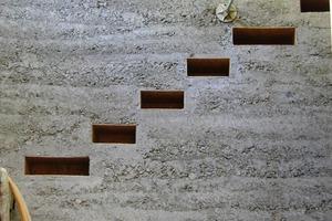 Schalungskörper in der aus Lehm gespampften Treppenhauswand zum Einschieben der Treppenstufen