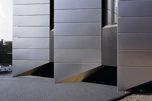 """<div class=""""10.6 Bildunterschrift"""">Für die Fassade, deren Struktur wie aufgefächert wirkt, wurden 12000m<sup>2</sup> eloxiertes Aluminium J57S von Nove-<br />lis in einer Stärke von 2mm als Glatt-<br />blechfassade unsichtbar verschraubt angebracht. Für die Dachverkleidung wurden weitere 3000m<sup>2</sup> benötigt</div>"""