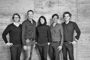 """<div class=""""fliesstext_vita""""><strong>kadawittfeldarchitektur</strong><br />v.l.n.r.: Stefan Haass, Gerhard Wittfeld, Jasna Moritz, Dirk Lange, Kilian Kada</div><div class=""""fliesstext_vita""""><br />von Klaus Kada und Gerhard Wittfeld 1999 in Aachen gegründet, realisiert das Büro mit derzeit 135 Mitarbeitern zahlreiche Projekte im In- und Ausland.</div>"""