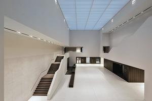 Eine Tageslichtdecke über dem Foyer bildet die Lichtstimmungen im Tageslichtverlauf ab, ergänzend sorgen Richtstrahler mit HIT und LED in den oberen Wandzonen für eine kraftvolle Beleuchtung. Licht aus linearen Deckengräben hebt die skulpturale Treppe hervor