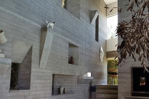 """<p><span class=""""ueberschrift_hervorgehoben"""">Die Sichtbetonwand mit eingelassenen Nischen und Öffnungen erinnert an Le Corbusiers Werk</span></p>"""