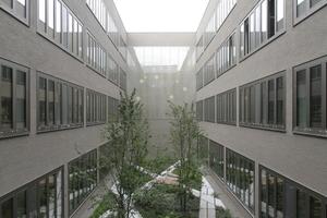 Blick in einen der Innenhöfe. Hinten die Glasfassade mit den leuchtenden Kugeln der Pendelleuchten in den Leseterrassen
